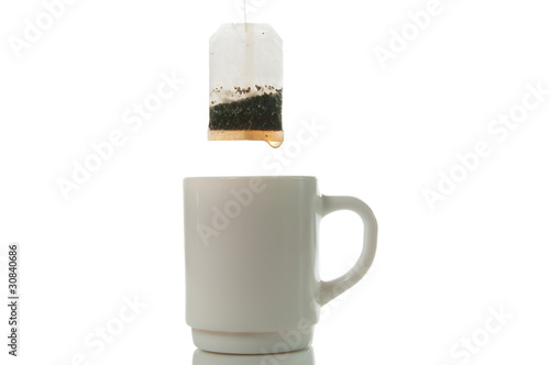 Tea bag over mug on a white background