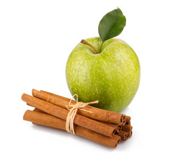 Ripe green apple with cinnamon sticks isolated