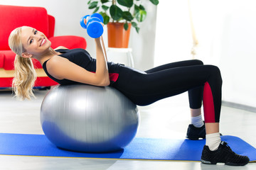 Woman doing fitness exercise with dumbbells on fit ball