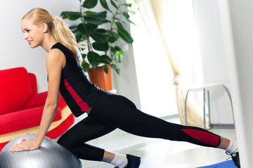 Woman in sportswear, doing fitness exercise with fit ball