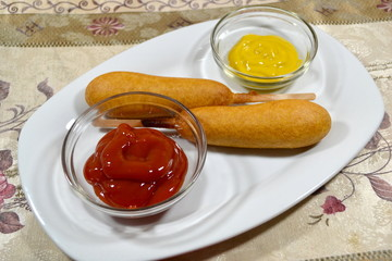 Two Corndogs with Mustard and Ketsup