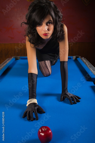 Sexy brunette with black gloves crawling on a pool table