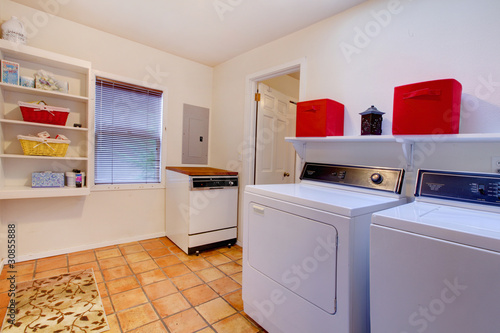 Laundry room with window and ceramic tile floor.