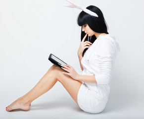 serious young woman sitting with tablet pc