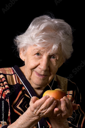 Apple in a hand of the old woman on the black