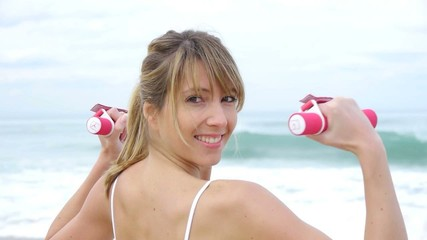 Blond woman doing fitness exercises on the beach