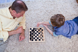 Grandfather playing chess with grandson on rug