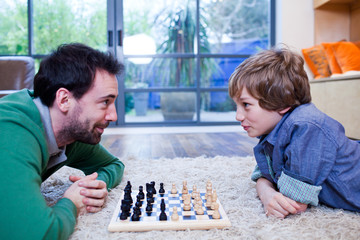 Father and son playing chess on rug