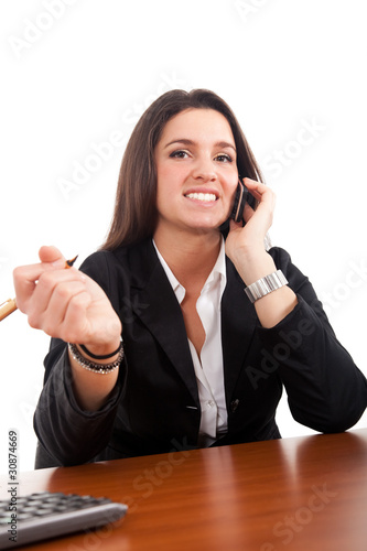 Businesswoman talking at the phone and working in her office