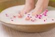 Leinwandbild Motiv schöne füße im rosenbad