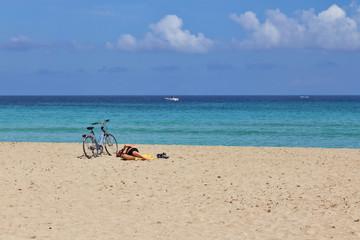 Ciclista disteso in relax sulla sabbia