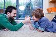 Father and son arm wrestling on rug