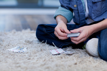 Boy playing cards on rug