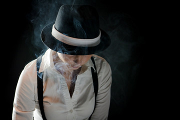 Mistic woman with black hat in smoke under cover