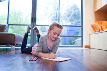 Girl drawing in sketchbook on wooden floor