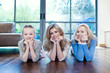 Grandmother, mother and daughter laying on wooden floor with head in hands