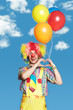 Portrait clown with balloons against the blue sky