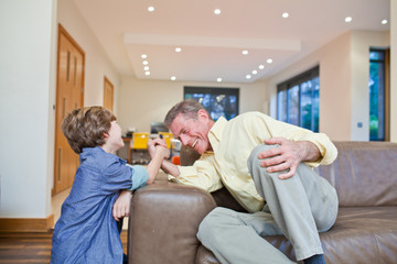 Grandfather and grandson arm wrestling on couch