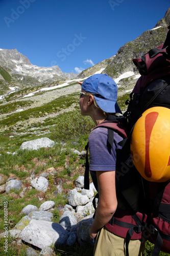 Girl with backpack looking to a mountains