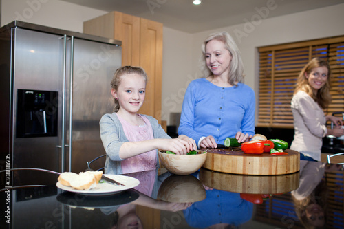 Grandmother, mother and daughter preparing healthy meal in kitchen