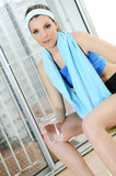 beautiful sportive woman is relaxing with a glass of water