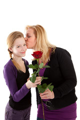 Young girl gives rose to mother over white background