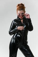 Sexy wouman in latex overalls in studio