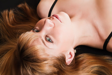 Pretty young woman lying on the black