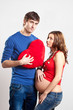 Couple of handsome man and pregnant woman with red heart
