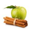 Ripe green apple with cinnamon sticks isolated