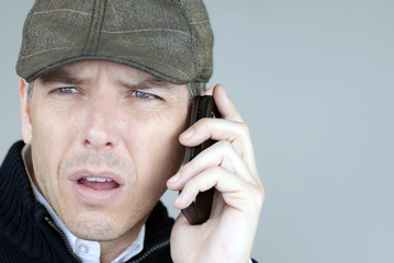 Worried Man In Newsboy Hat On Phone