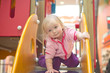 adorable baby prepare to slide down slide on playground in mall