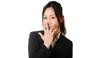 口に手を当てて驚くスーツの女性
