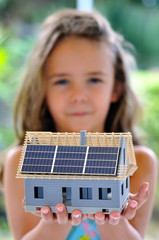 Fillette présentant une maquette de maison.