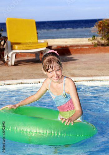 Child sitting on inflatable ring.