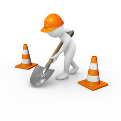 Construction worker digging the ground with traffic cones around