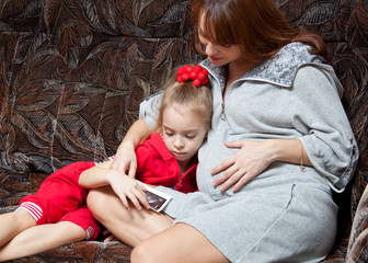 a pregnant woman with her daughter looks at picture on the sofa