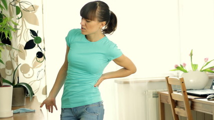 Woman having back pain during housekeeping