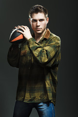 Young man whith ball in studio
