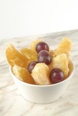 Bol con gajos de naranja y uvas