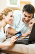 Couple with laptop, paying by credit card, at home