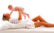 Junge Mutter spielt mit ihrem Sohn auf dem Bett