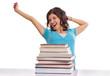 Frau streckt sich hinter Bücherstapel