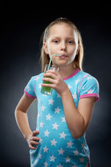 Little girl drinking juice, studio shot