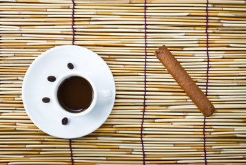 coffee in cup, cigar and coffee beans on bamboo