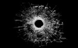 bullet hole in glass isolated on black