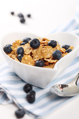 cereal with fresh blueberries and spoon on white background