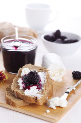 Breakfast with bread, blackberry jam and fresh goat cheese