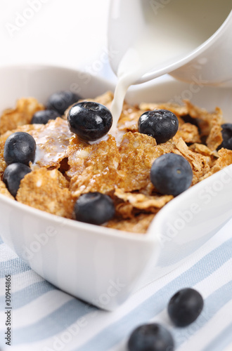 milk pouring into cereal with fresh blueberries