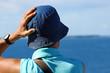 femme au chapeau de toile face à la mer